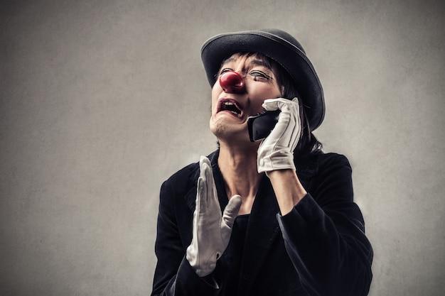 Weinender trauriger clown, der am telefon spricht