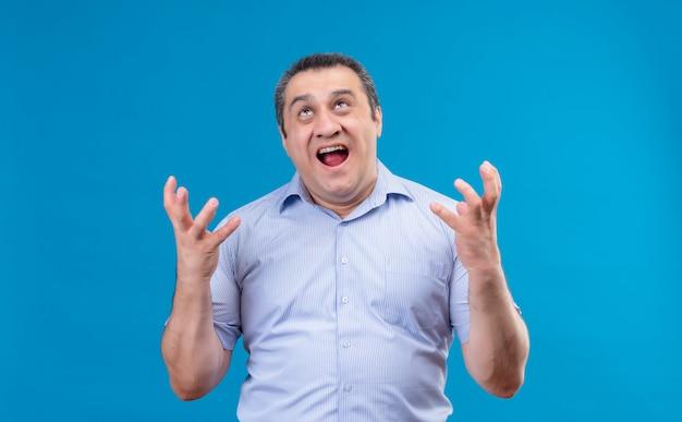 Weinender und wütender mann mittleren alters im blau gestreiften hemd, der hände auf einem blauen raum schreit