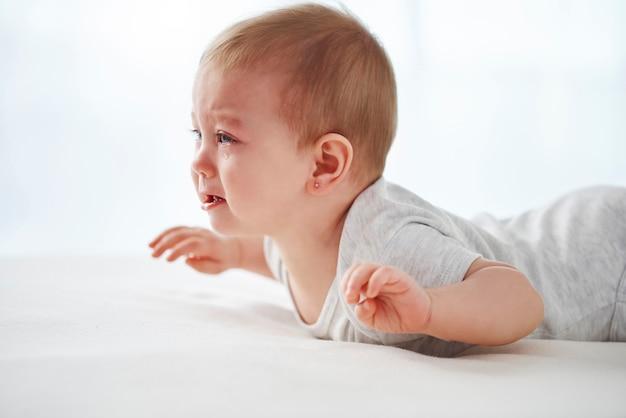 Weinendes baby liegt auf dem bett