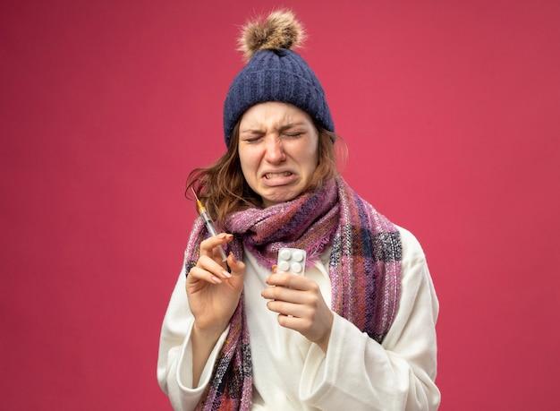 Weinendes junges krankes mädchen, das weiße robe und wintermütze mit schal hält spritze mit pillen auf rosa isoliert trägt