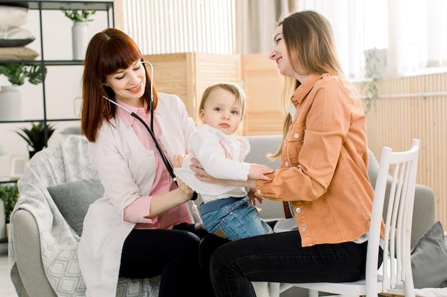 Weinendes krankes kindbaby auf mutterhänden im krankenhaus oder zu hause, und ärztin, die untersuchung untersucht