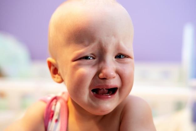 Weinendes mädchen bei der stellung in ihrer krippe.