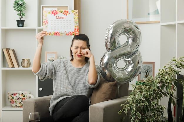 Weinendes schönes mädchen am glücklichen frauentag, der den kalender hält, der auf einem sessel im wohnzimmer sitzt