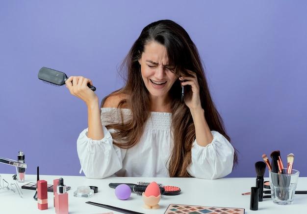 Weinendes schönes mädchen sitzt am tisch mit make-up-werkzeugen hält haarkamm, der am telefon spricht, lokalisiert auf lila wand