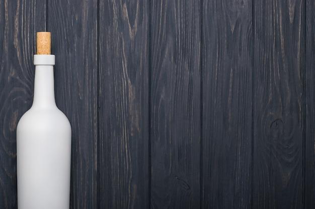 Weinflasche auf dunklem hölzernem hintergrund.