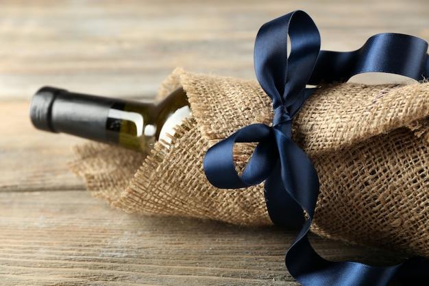 Weinflasche eingewickelt in sackleinen stoff auf holzbretter hintergrund