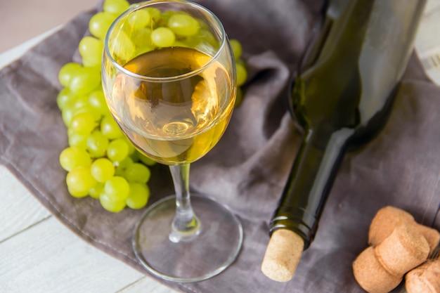 Weinflasche, glas, trauben auf tabelle. ansicht von oben