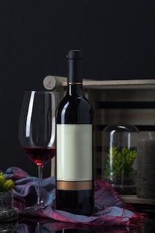 Weinflasche mit becher, pflanze, schal, kerze und holzkiste
