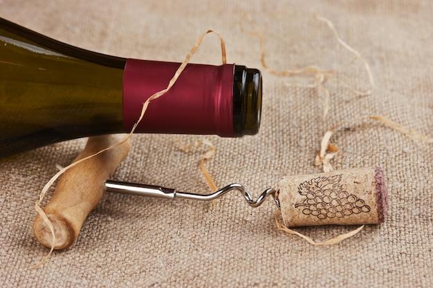 Weinflasche und korkenzieher auf leinwand, stillleben
