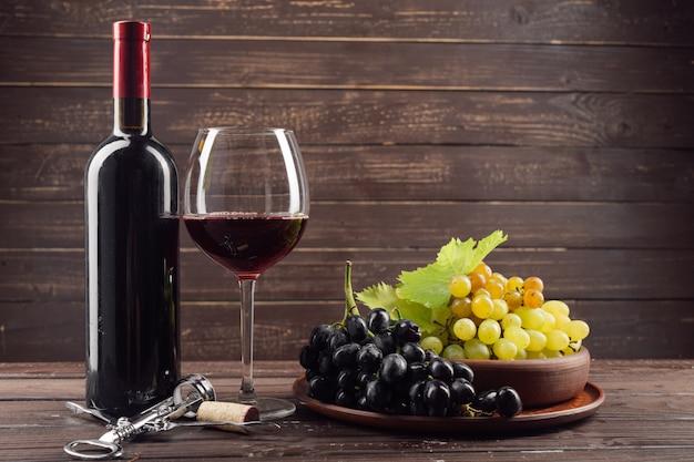Weinflasche und -traube auf holztisch