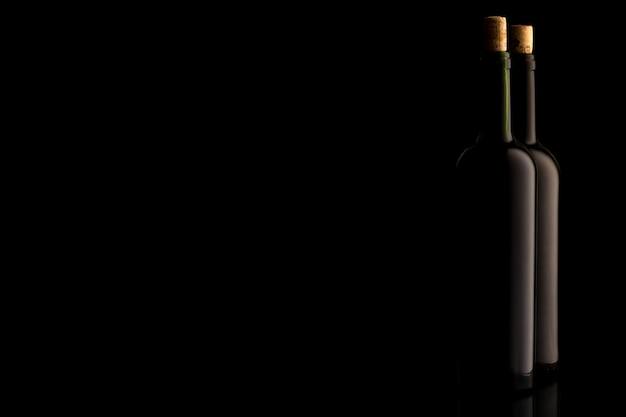 Weinflaschen mit kork und auf schwarzem isoliertem hintergrund