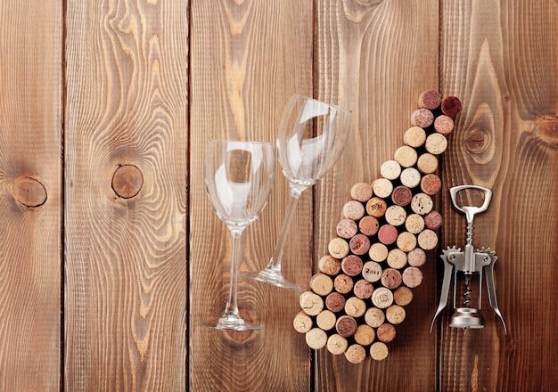 Weinflaschenförmige korken, gläser und korkenzieher über rustikalem holztischhintergrund. ansicht von oben mit kopienraum