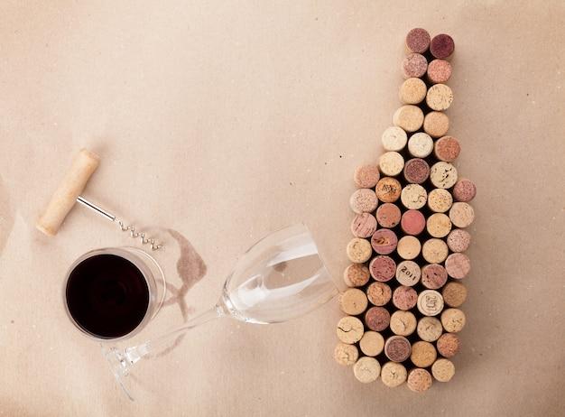 Weinflaschenförmige korken, glas wein und korkenzieher über papppapierhintergrund. ansicht von oben mit kopienraum