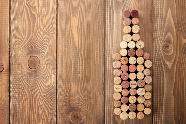 Weinflaschenförmige korken über rustikalem holztischhintergrund. ansicht von oben mit kopienraum