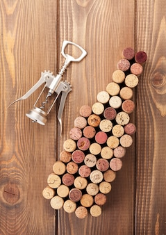 Weinflaschenförmige korken und korkenzieher über rustikalem holztischhintergrund. sicht von oben