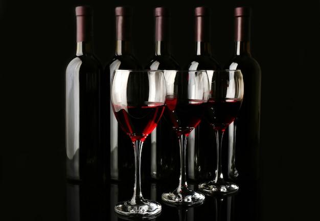 Weingläser gegen flaschen in einer reihe auf schwarzem hintergrund