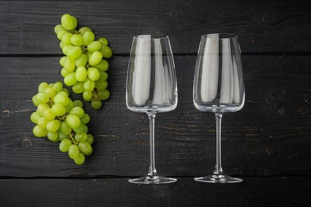 Weingläser mit trauben gesetzt, auf schwarzem holztisch tisch, draufsicht flach legen