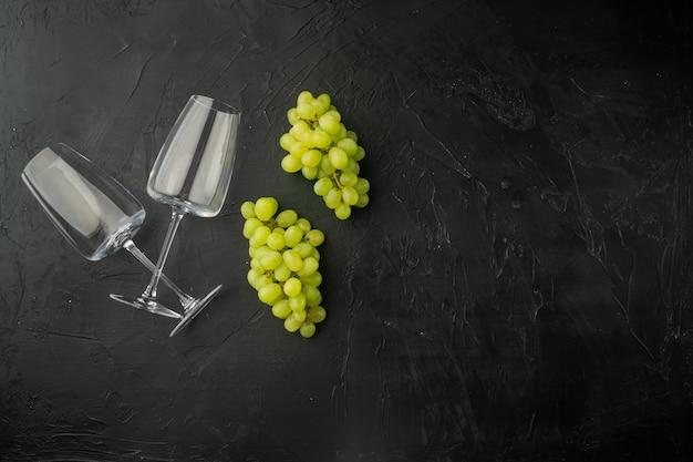 Weingläser mit trauben gesetzt, auf schwarzem steintisch, draufsicht flach gelegt