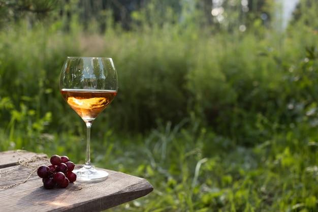 Weinglas auf einem holztisch in einem sommergarten am abend