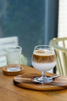 Weinglas eiskaffee zwei schichten frische milch und espresso kurz auf holztisch im café. erfrischendes sommergetränkekonzept. (nahaufnahme, selektiver fokus)