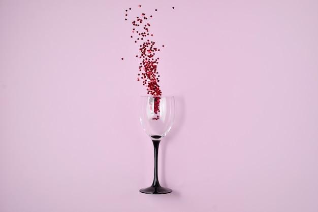 Weinglas goss heraus rote herzkonfettis auf rosa farbpapierhintergrund.