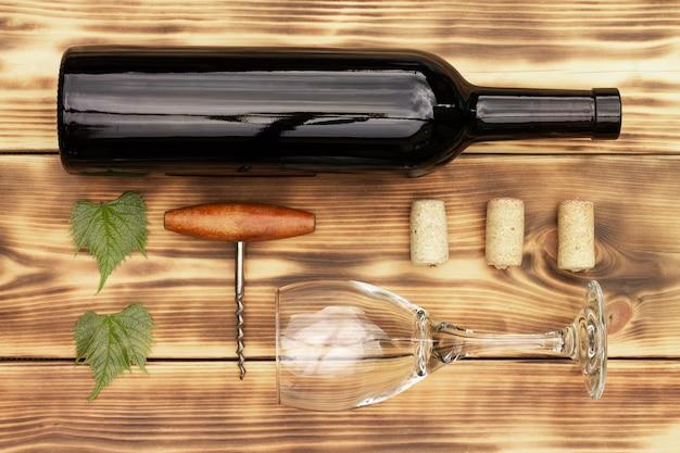 Weinglas, korkenzieher, korken, weinflaschen, weinrebe auf rustikalem, gebranntem holzhintergrund. ansicht von oben. platz kopieren