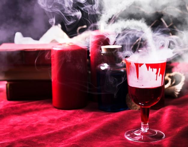 Weinglas mit blutigen tropfen und halloweenzeug
