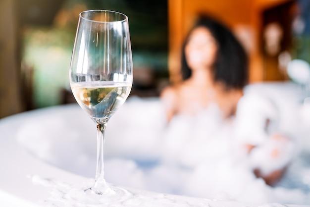 Weinglas mit frau, die im hydromassagebad entspannt
