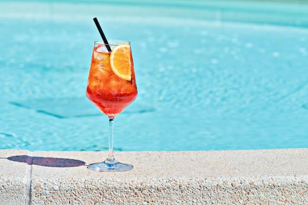 Weinglas mit kaltem cocktail aperol spritz gegen türkisfarbenes wasser am pool