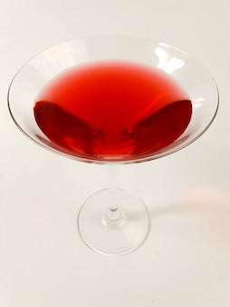 Weinglas mit rotem martini auf weißem hintergrund