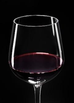 Weinglas mit rotwein auf schwarzem hintergrund