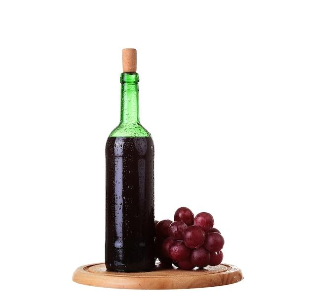 Weinglas mit rotwein, flasche wein und trauben an bord lokalisiert über weißem hintergrund