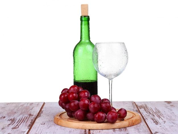 Weinglas mit rotwein, flasche wein und trauben getrennt über weißem hintergrund