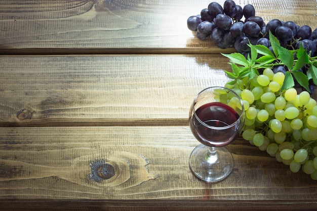 Weinglas mit rotwein und reifer traube auf hölzernem brett. close up und kopieren sie platz.