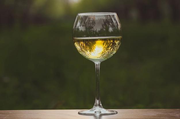 Weinglas mit weißwein im blühenden apfelgarten