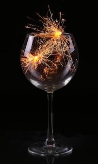 Weinglas mit wunderkerze in erwartung von neujahr und weihnachten
