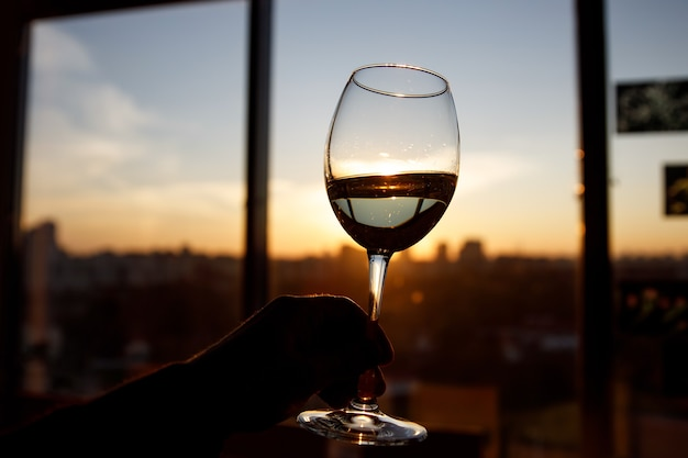 Weinglas über sonnenuntergang. fenster und stadt im hintergrund.
