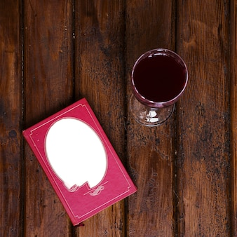 Weinglas und buch auf altem holz