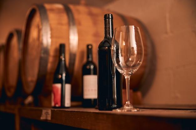 Weinglas und flasche alkoholisches getränk auf holzregal im weinkeller