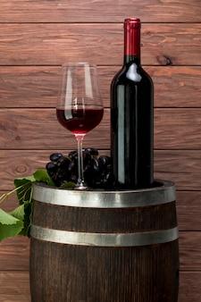 Weinglas und flasche auf einem fass