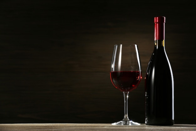 Weinglas und flasche auf hölzernem hintergrund
