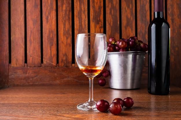 Weinglas und weinflasche mit roten trauben auf hölzernem hintergrund