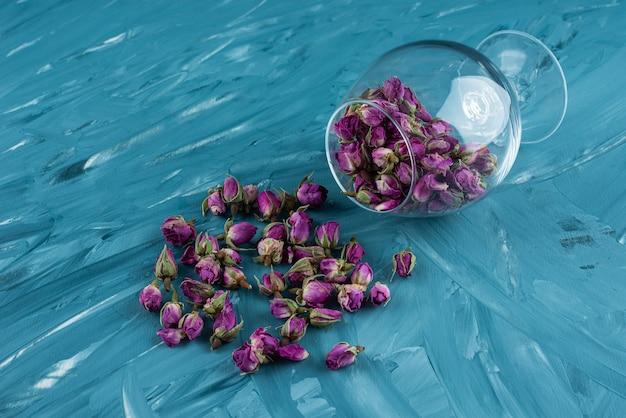 Weinglas voller getrockneter rosenblütenknospen, die auf blauem tisch liegen.