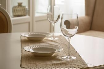Weingläser und weiße Platten auf Tabelle im Esszimmer