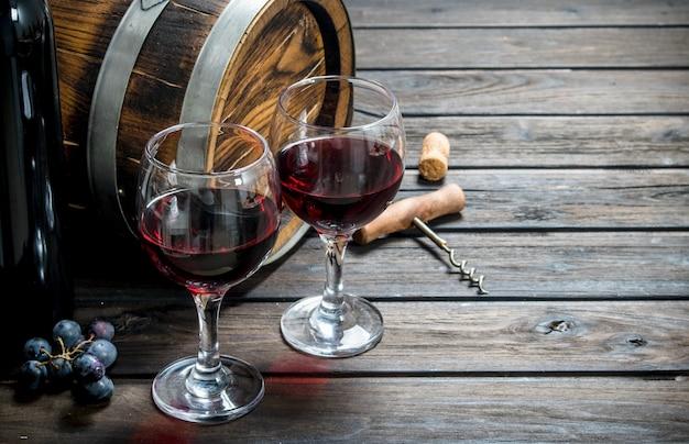 Weinhintergrund. ein altes fass rotwein. auf einem hölzernen hintergrund.