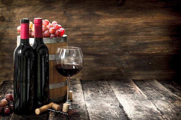 Weinhintergrund. ein fass mit rotwein und frischen trauben. auf einem hölzernen hintergrund.
