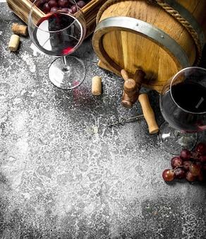 Weinhintergrund. ein fass mit rotwein und frischen trauben. auf einem rustikalen hintergrund.