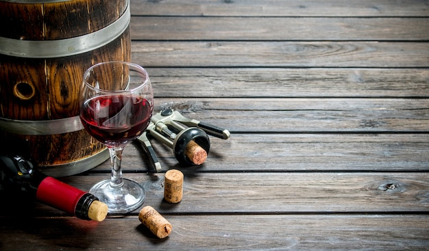 Weinhintergrund. ein fass rotwein mit einem korkenzieher. auf einem hölzernen hintergrund.