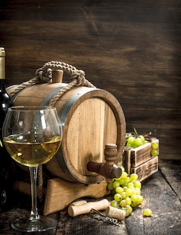 Weinhintergrund ein fass weißwein mit zweigen der grünen trauben auf einem hölzernen hintergrund