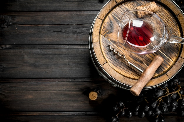 Weinhintergrund. fass mit rotwein und trauben. auf einem hölzernen hintergrund.
